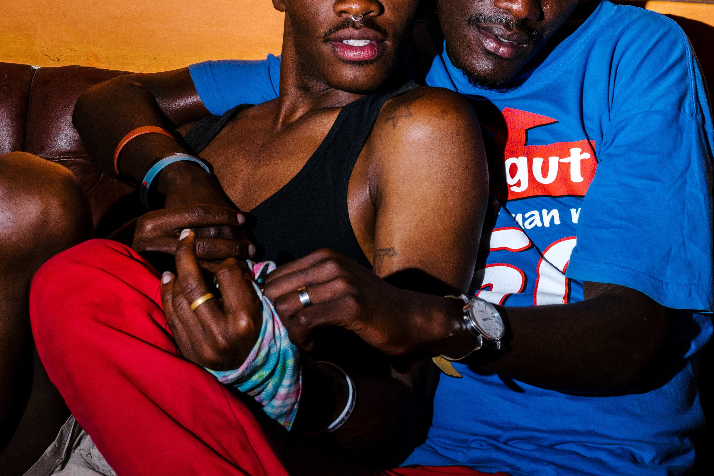 A couple, both gay refugees from Uganda, pose for a portrait outside the home they lived in in a town just outside of Nairobi, Kenya.