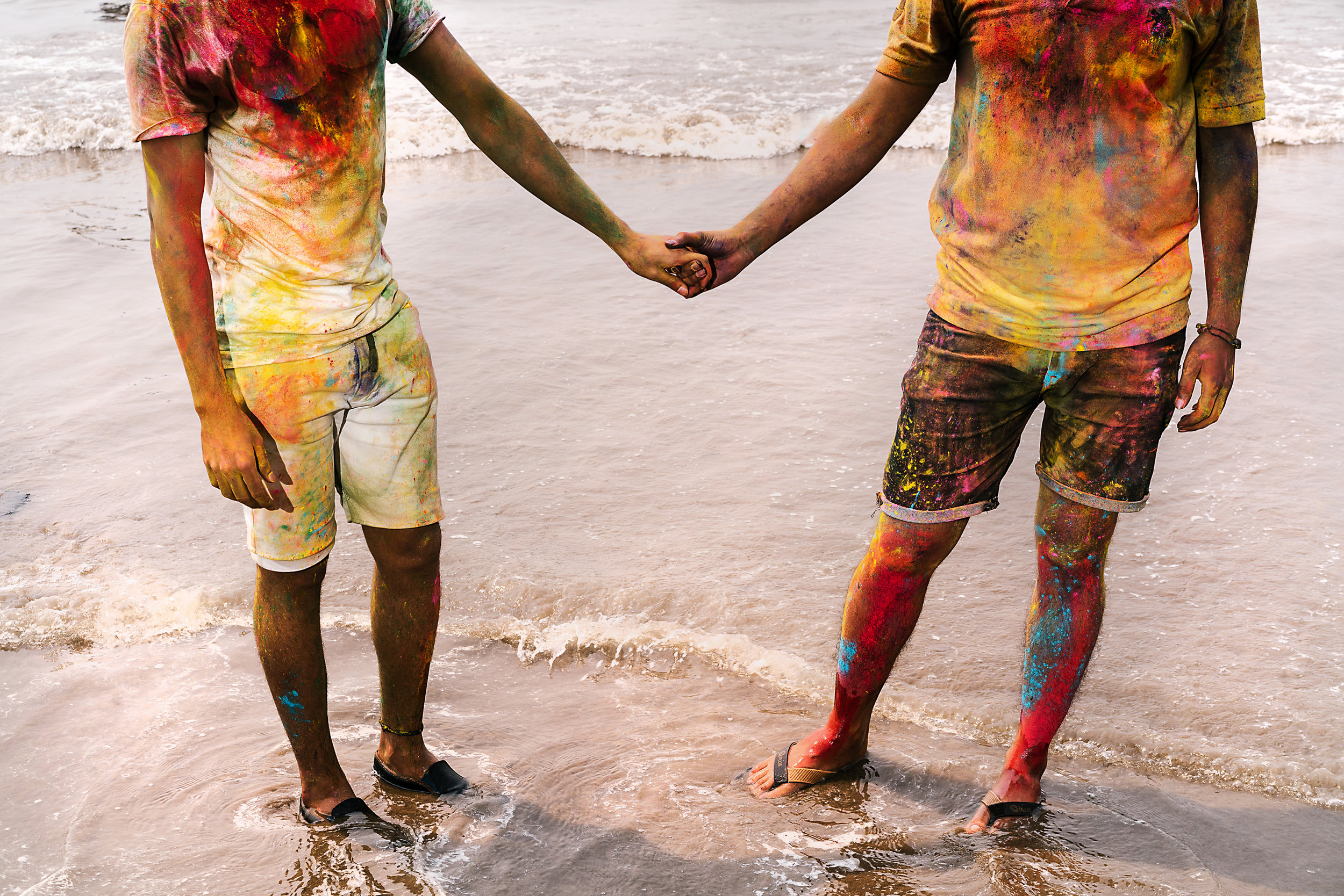Two friends play Holi along with other LGBTQ people at Juhu Beach in Mumbai at an outing organized by Gay Bombay.