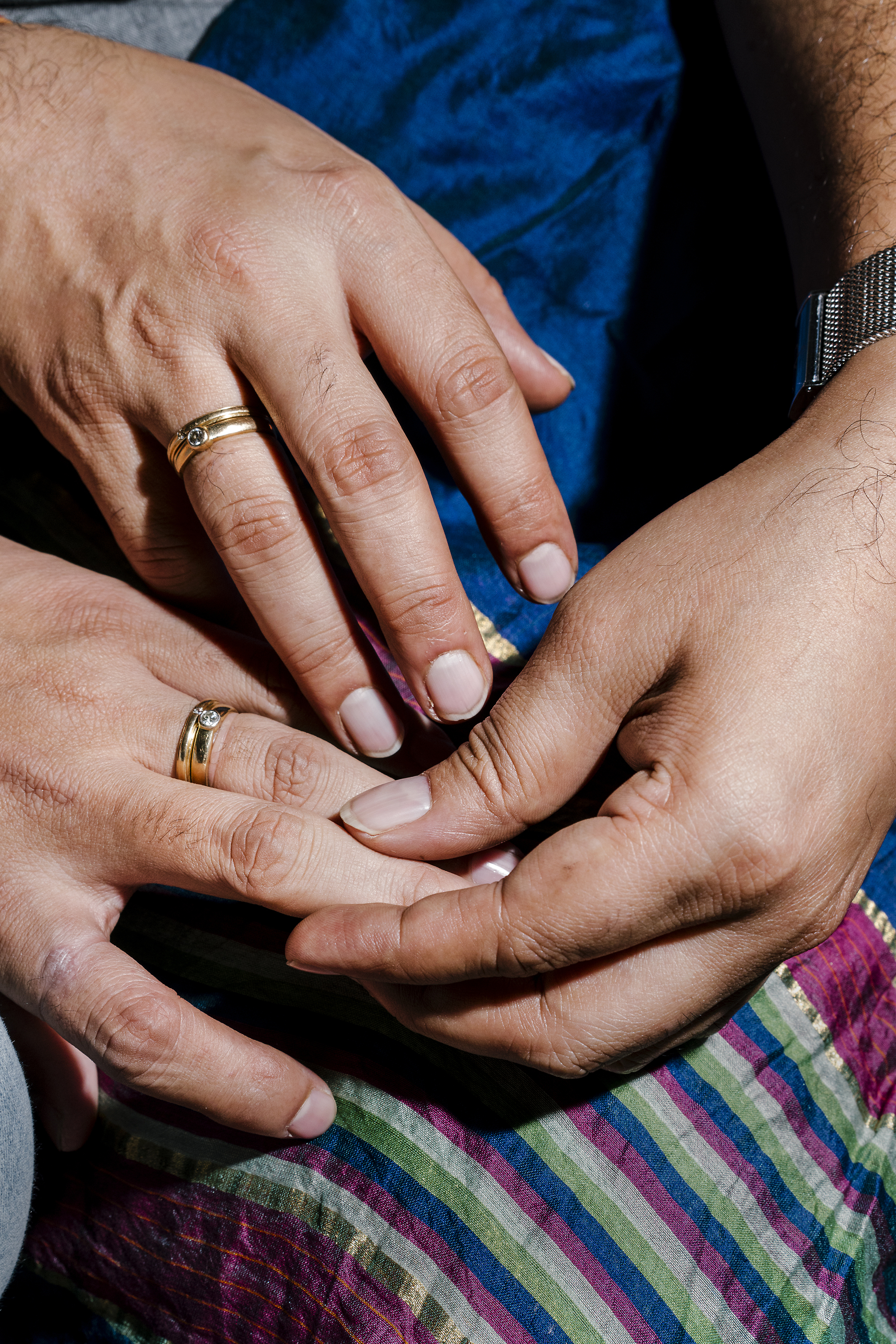 A gay married couple display their wedding rings. They declined to share their names or faces out of fear of how their parents will react when they discover the news.