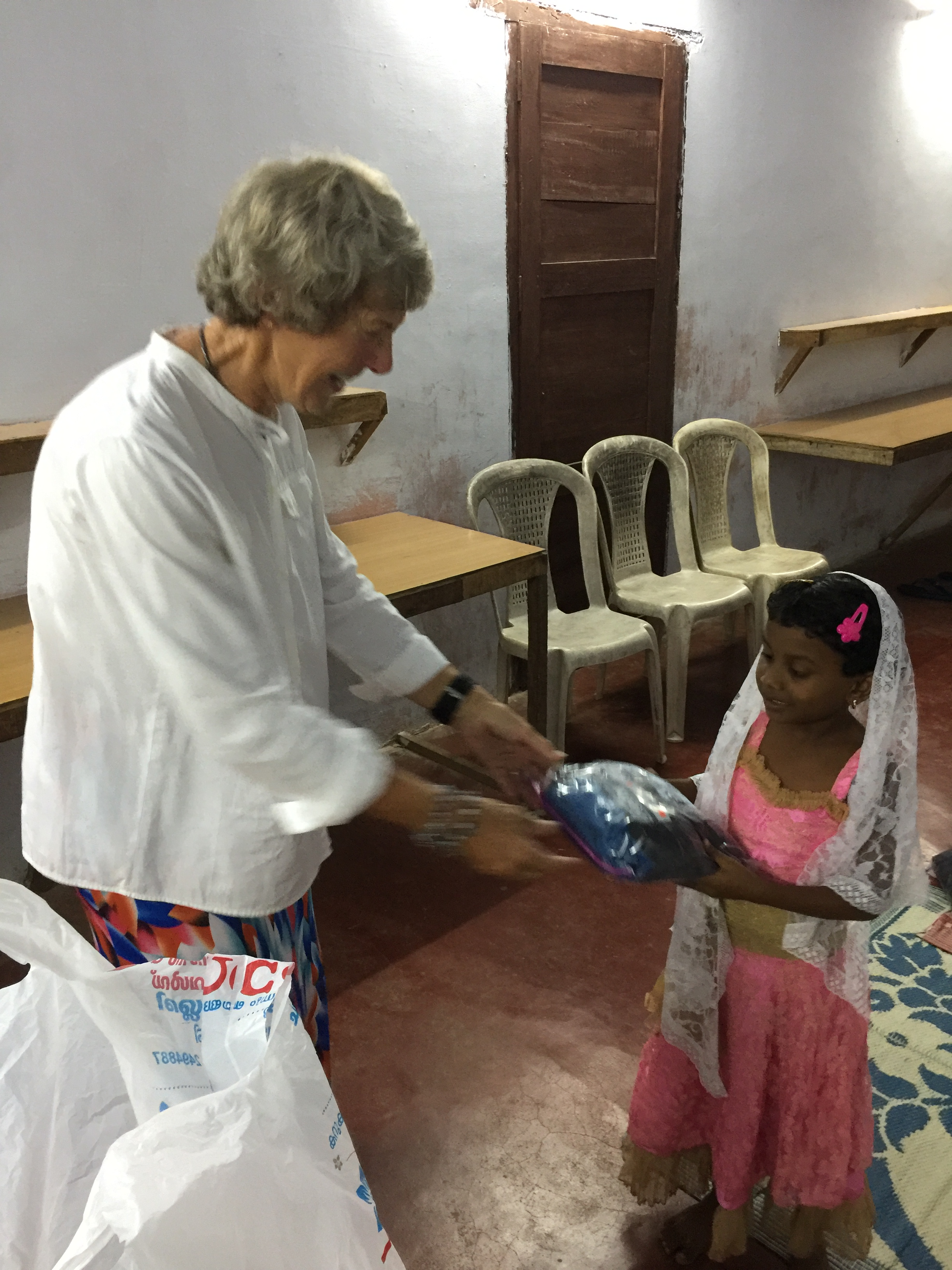 Hennie purchased cloths for children and Carol Grosvenor send some gifts for staff at orphanage. Hennie is distributing.