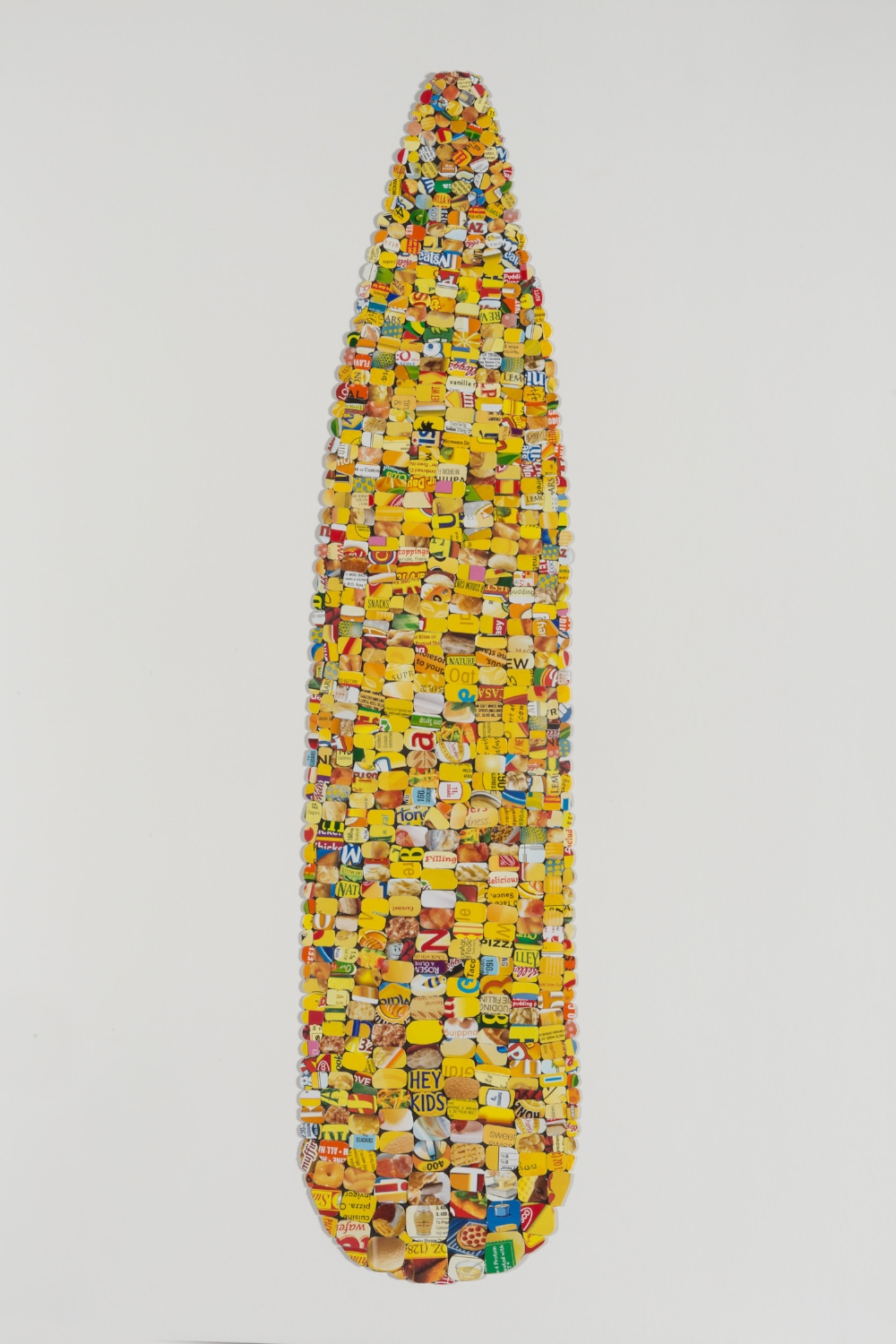 """Questionable Foods, Corn #1 , 2016, 33""""h x 11""""w framed, discarded food boxes, mixed media."""