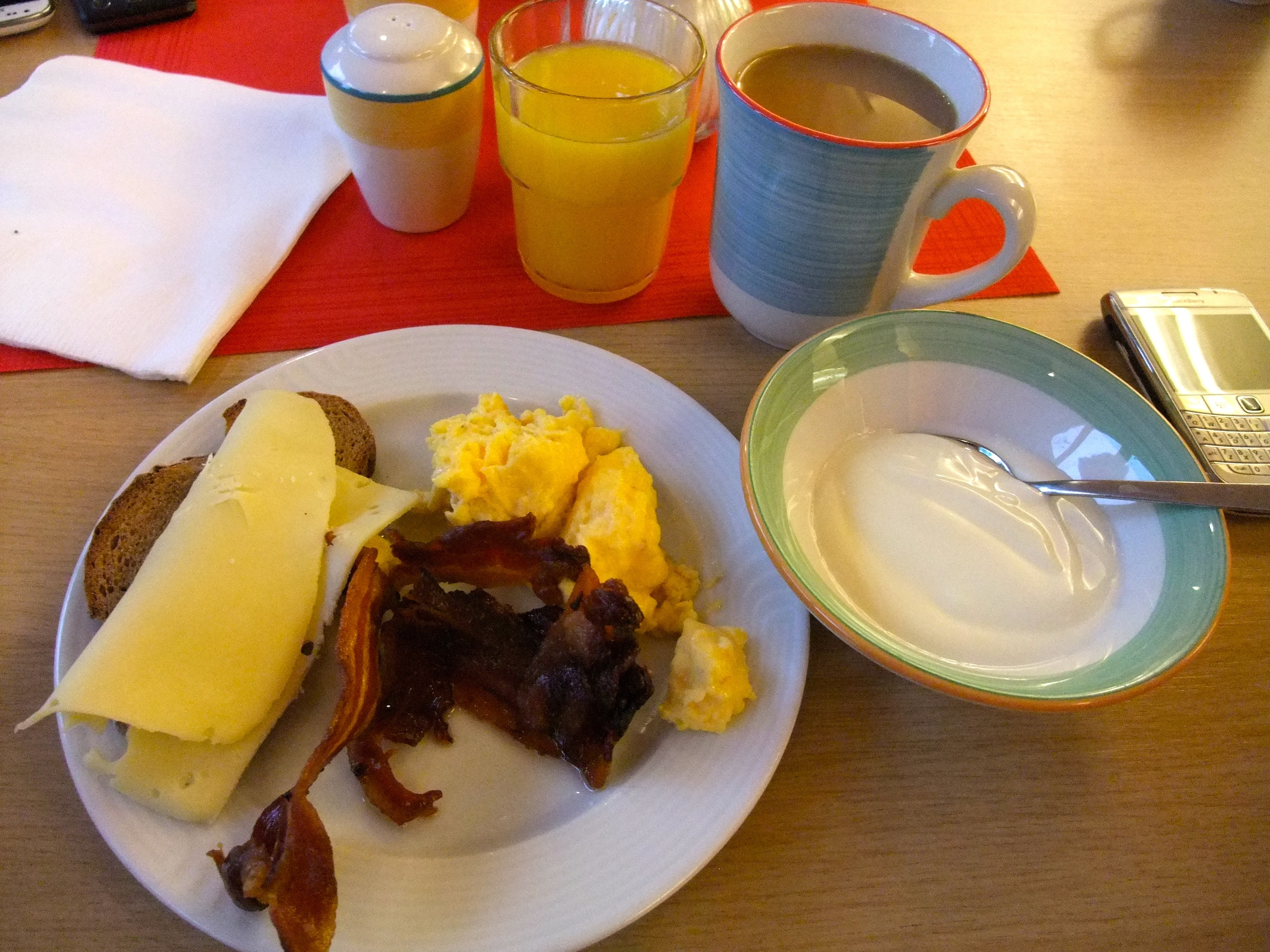 Breakfast of bread, cheese, bacon, eggs, yogurt, coffee, and orange juice