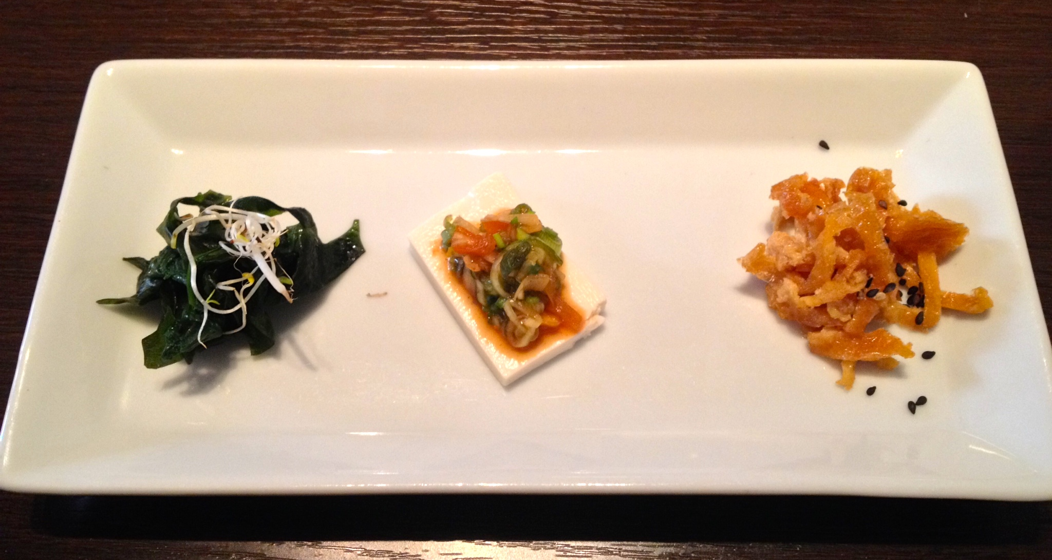 Appetizers from left to right: seaweed salad, soft tofu with a green onion topping, strips of pan-fried sweet tofu