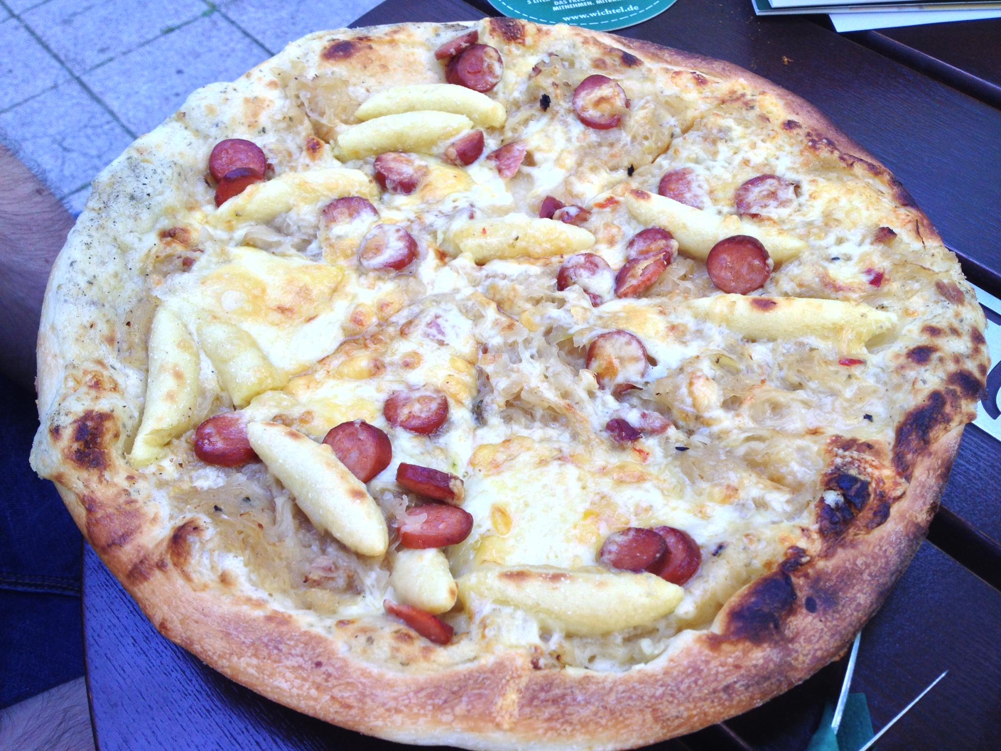 Wichtelkuchen with cream, cheese, bacon, sauerkraut, schupfnudeln, and spicy debrecener sausage