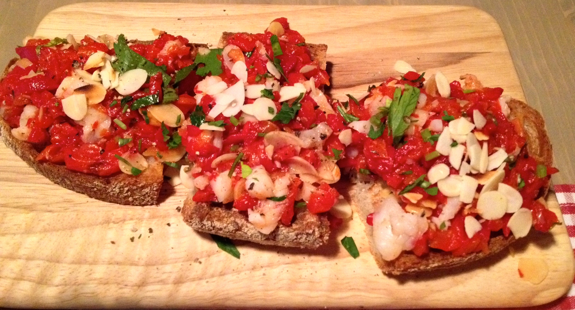 Toasted bread with shrimp, piquillo peppers, and roasted almonds
