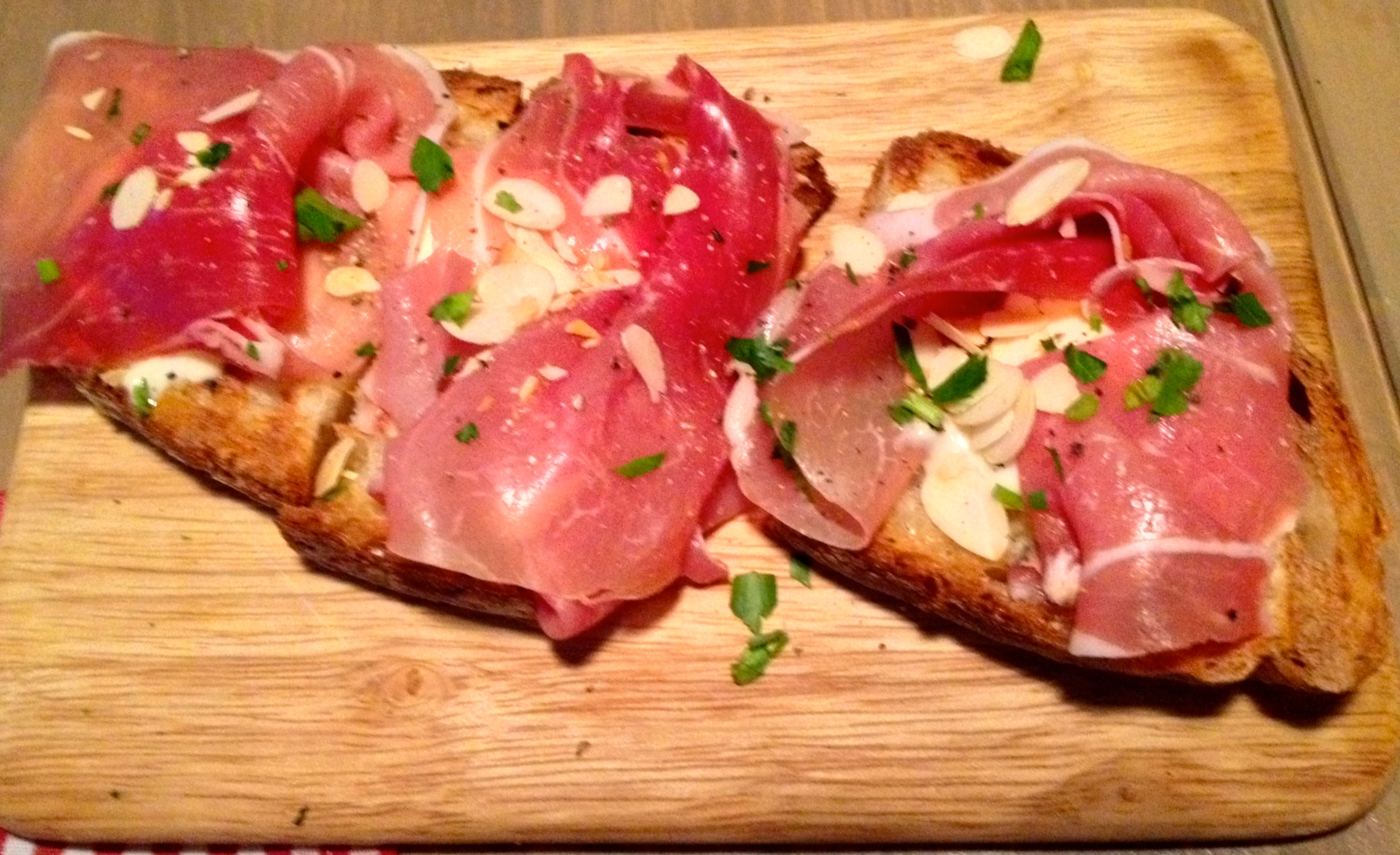 Toasted bread with Serrano ham, garlic aioli, and roasted almonds