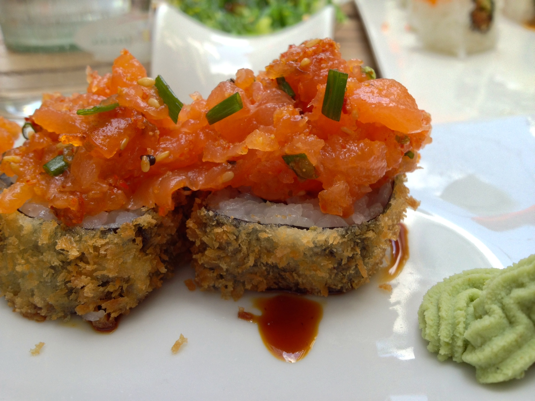 Fried avocado roll topped with spicy salmon