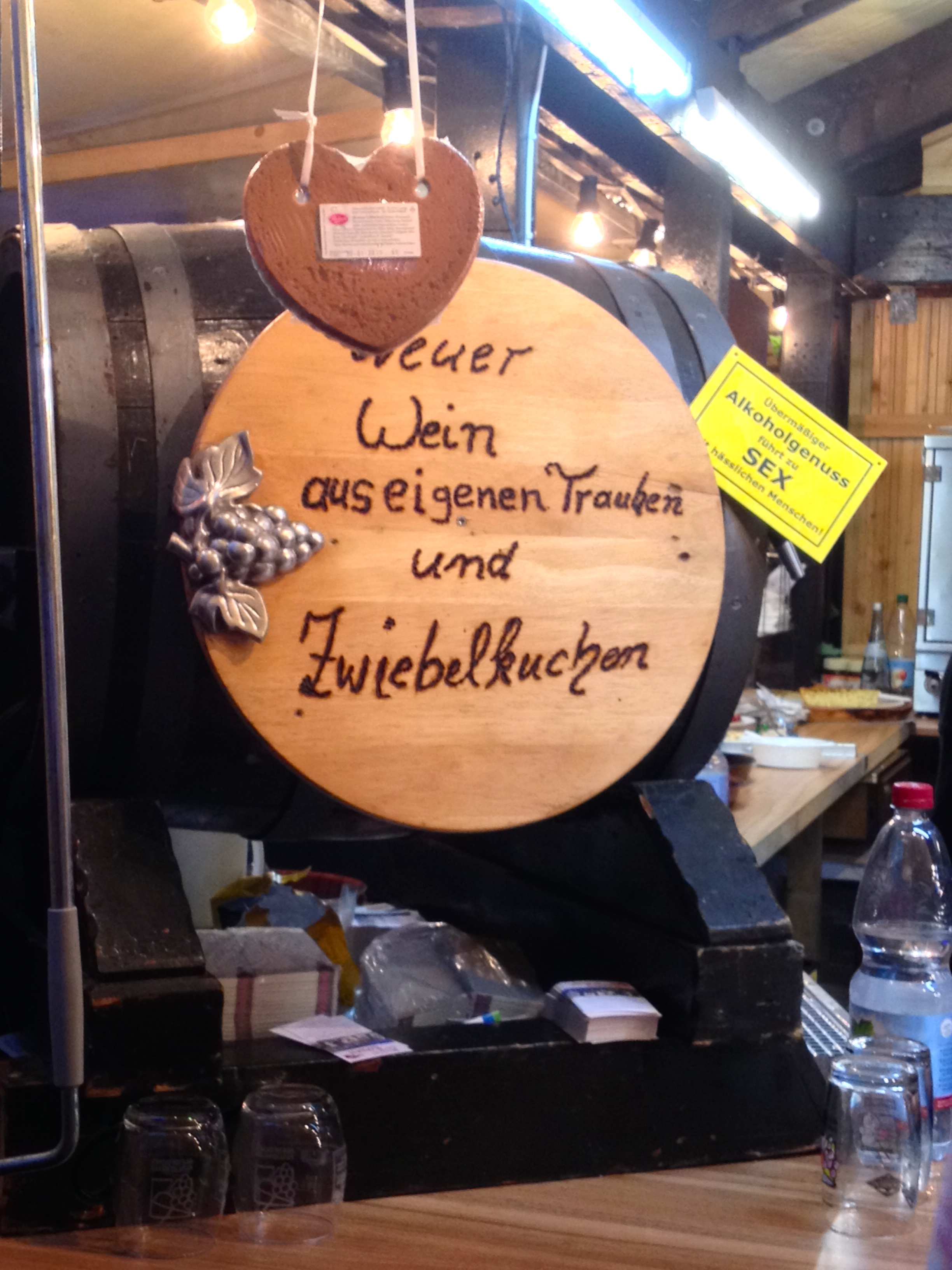 """A cask of Neuer Wein and a yellow sign warning, """"Excessive alcohol consumption leads to sex with ugly people."""""""