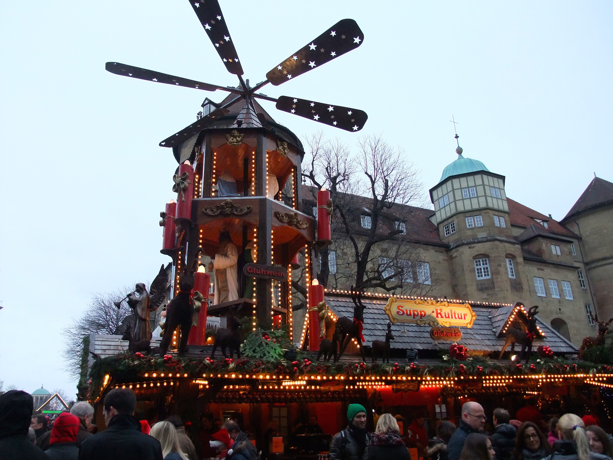 A Christmas pyramid on top of a stall next to the old castle
