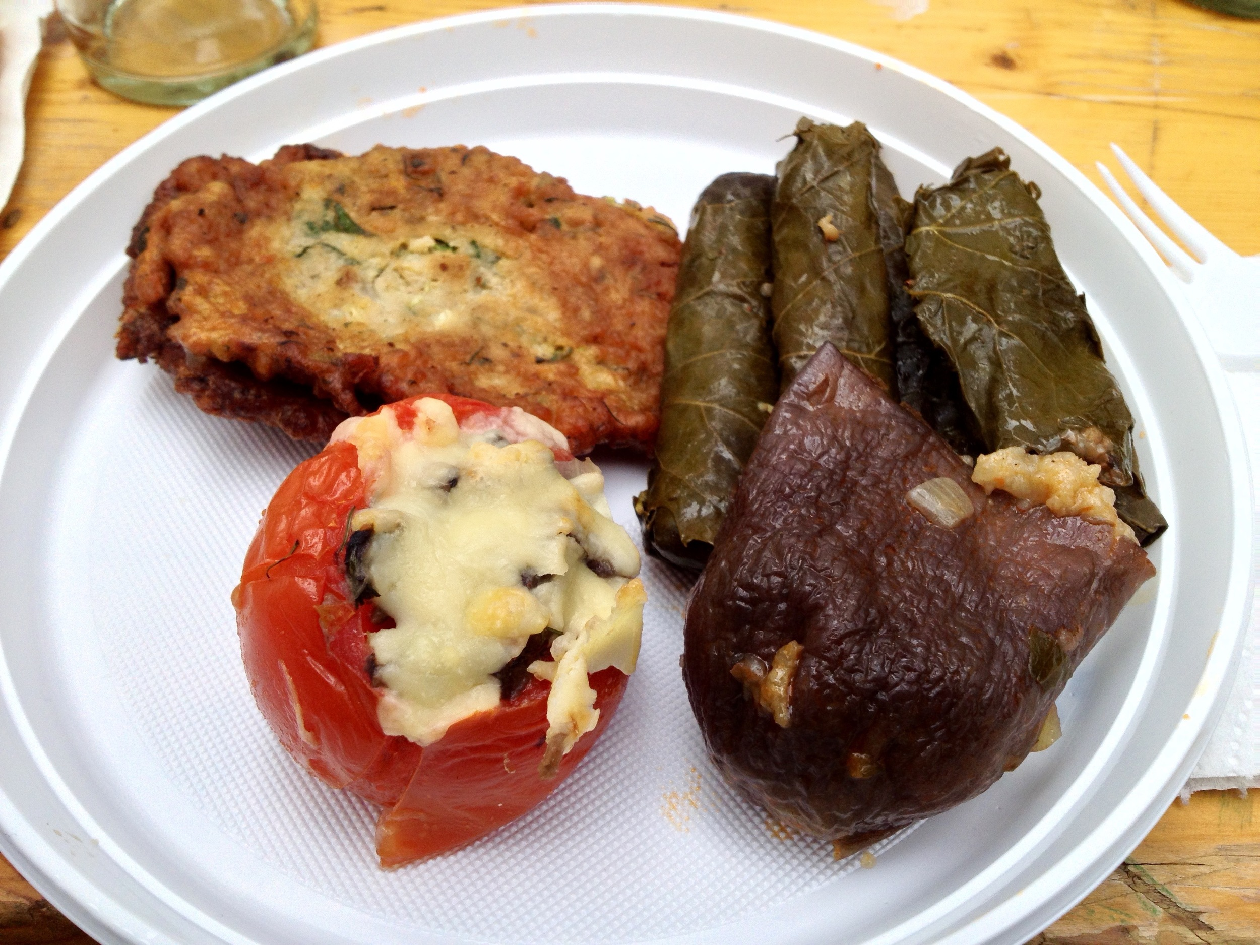 Clockwise from the top left: zucchini patties, stuffed grape leaves, stuffed eggplant, and a stuffed tomato