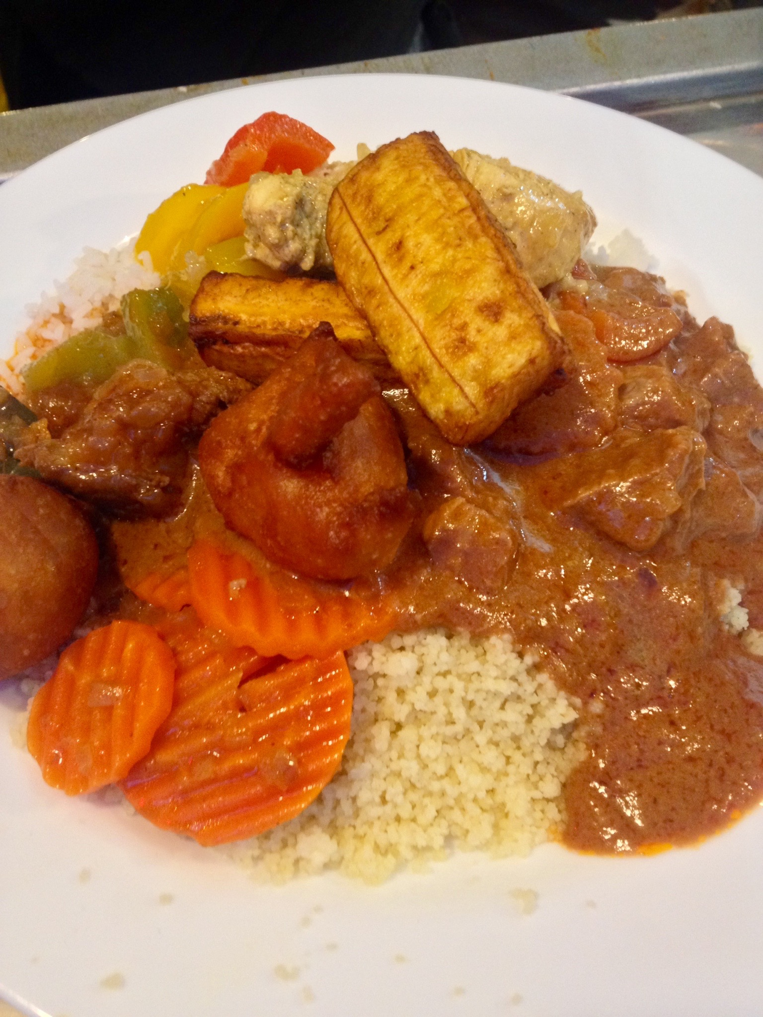 Mixed plate of beef, chicken, and lamb with vegetables on rice and couscous