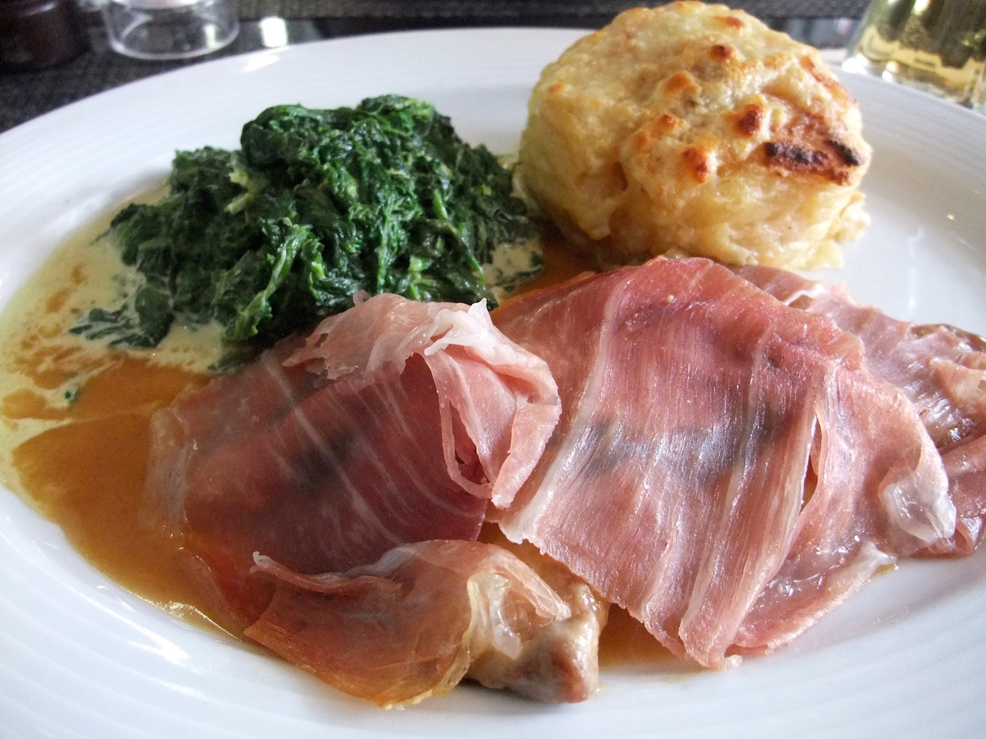 Veal topped with Parma ham in a sage sauce with creamed spinach and potato gratin