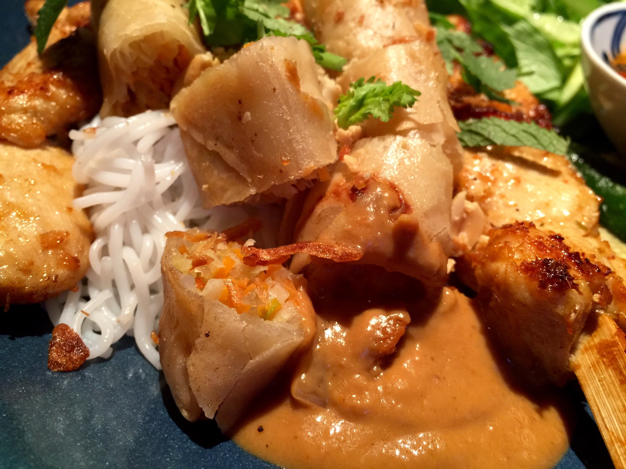 A close up shot of my fried spring rolls, lemongrass chicken skewers, and peanut sauce over rice noodles