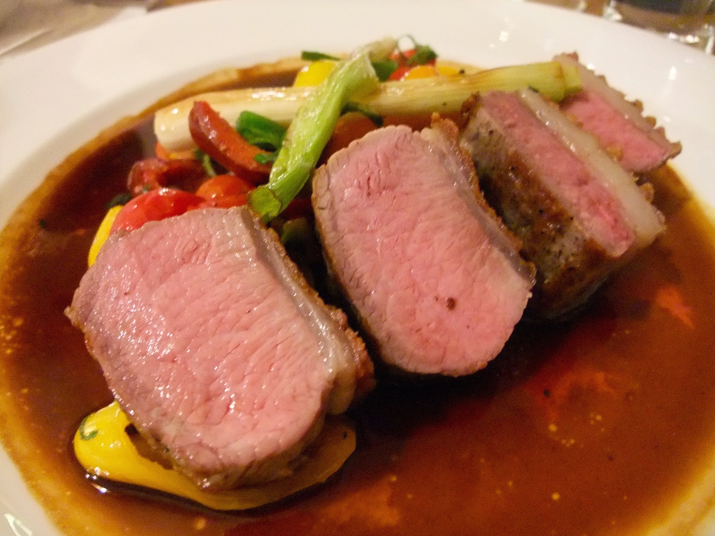 Lamb entrée with sautéed peppers in a red wine sauce