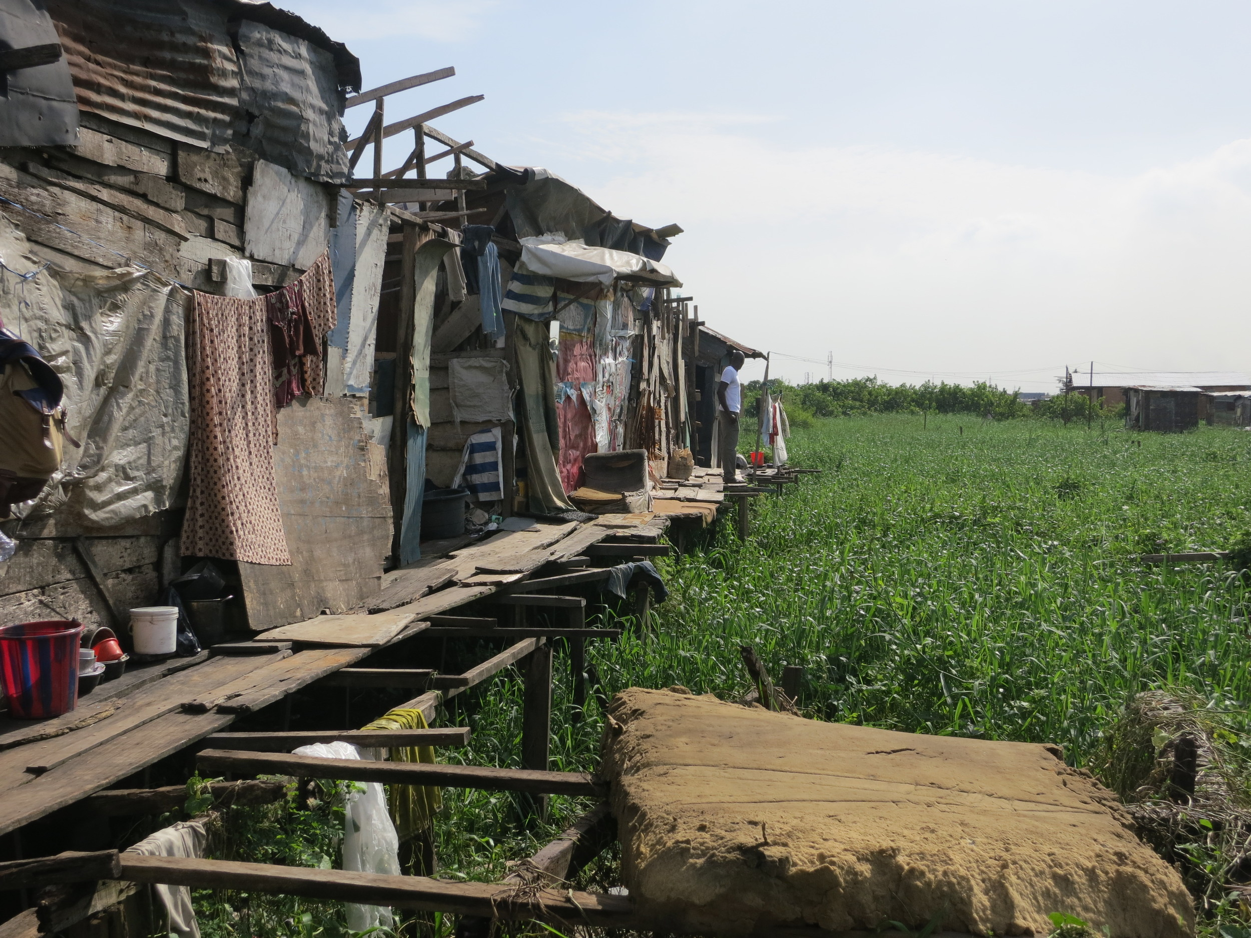 With rapid migration into cities and high birth rates, there is intense pressure on land in urban centers, resulting in innovative building solutions, like shacks on stilts above swamps and drainages.