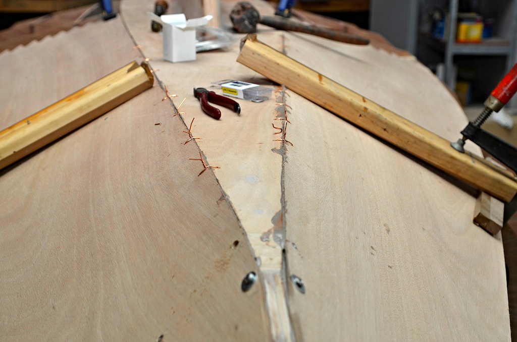 The sole and garboard are attached stitch and  glue style, this is the froward panel being glued in, I used copper wire from a local electrical shop to hold the panels together as well as the clamps and screws.