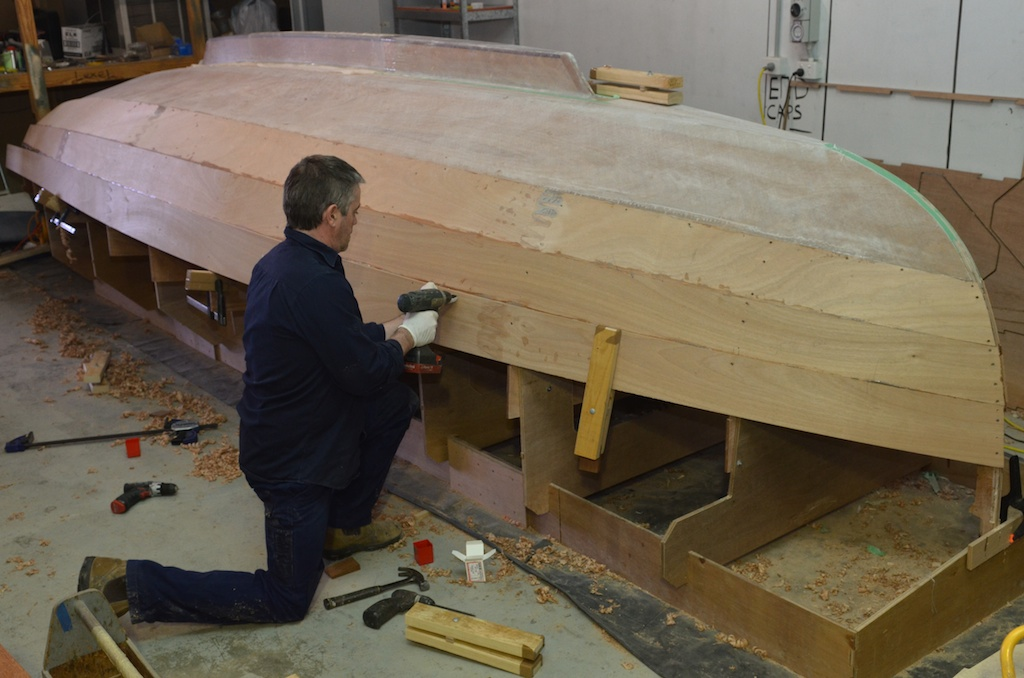 Fitting fourth plank, the wooden clamp helps to hold the edges together, small screws are also used.