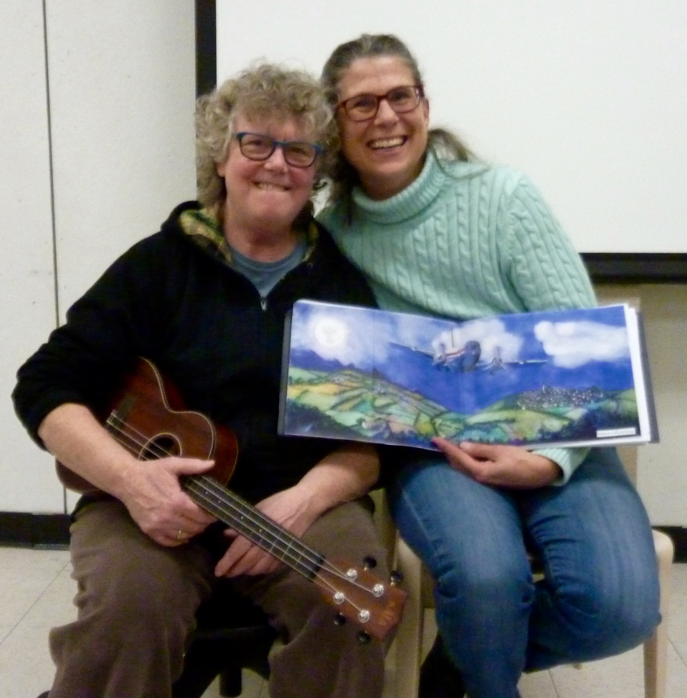 Cheryl Wheeler with her ukulele, and Manette with a color copy of her finished illustration inserted into the dummy.