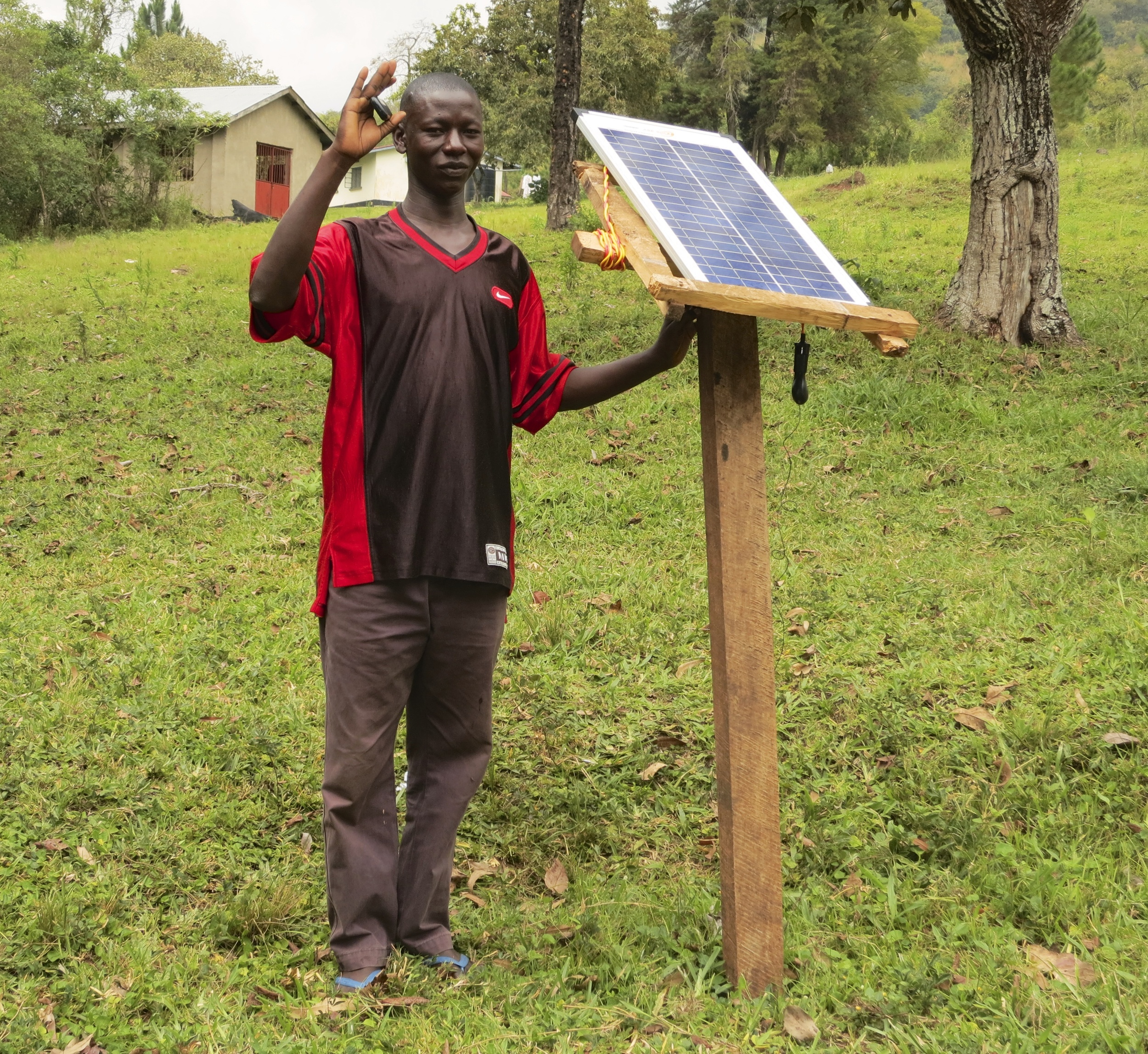 Charging his cell phone at a solar panel.  Solar energy widespread because electricity infrastructure is unreliable.