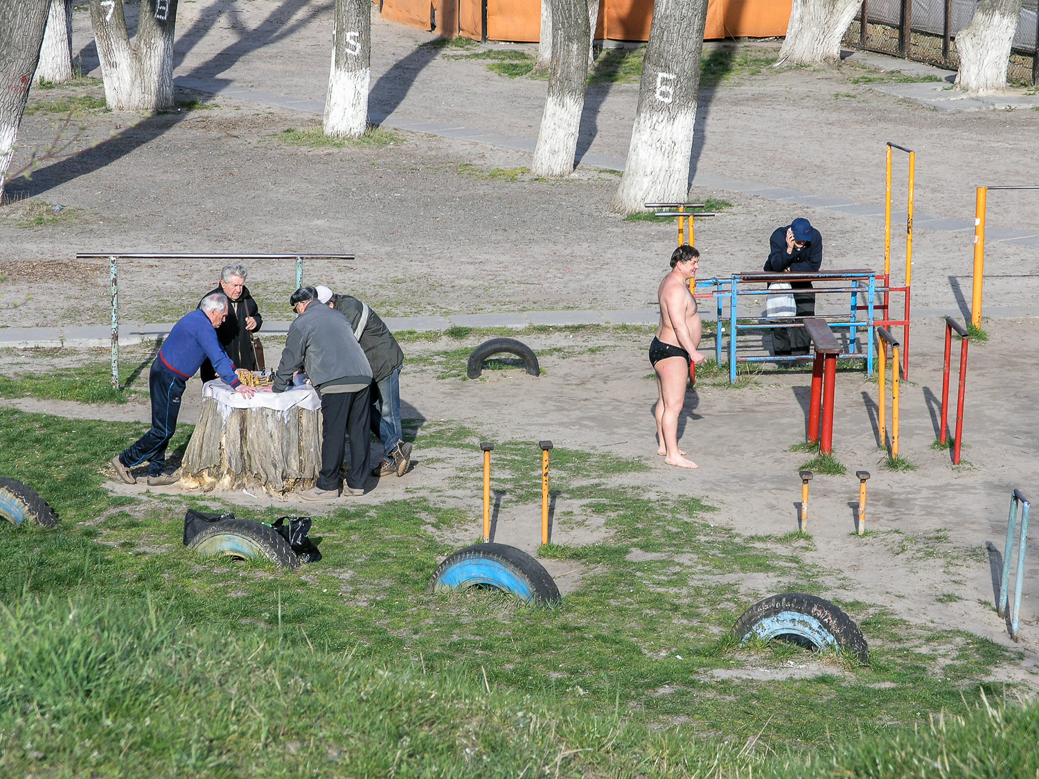 Men playing chess in a playground on 'Hidropark', an island in the middle of the Dnieper river in Kiev. The island is a popular place for recreation in the summer months.