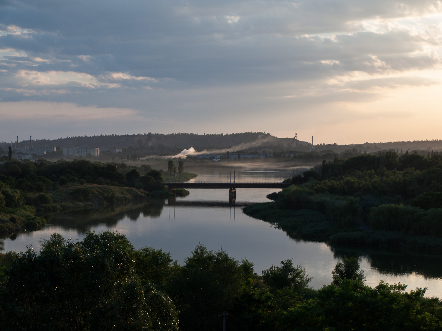 A view over the Inhulets river at Kryvyi Rih. Headframes for the city's numerous iron ore mines are visible in the background.