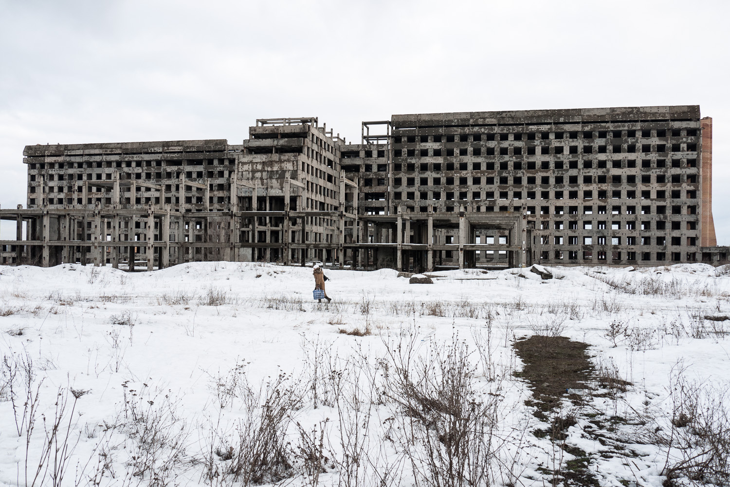 A woman walks past an abandoned building in Donetsk, east Ukraine.