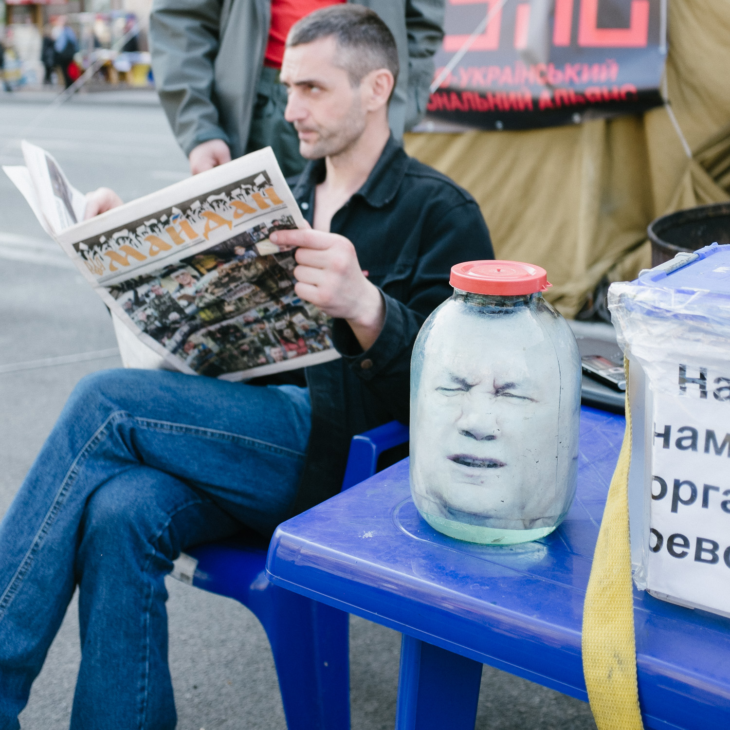 A man reads from a free newspaper reporting on the Euromaidan uprisings next to a replica head of former president Viktor Yanukovych in a sealed jar.