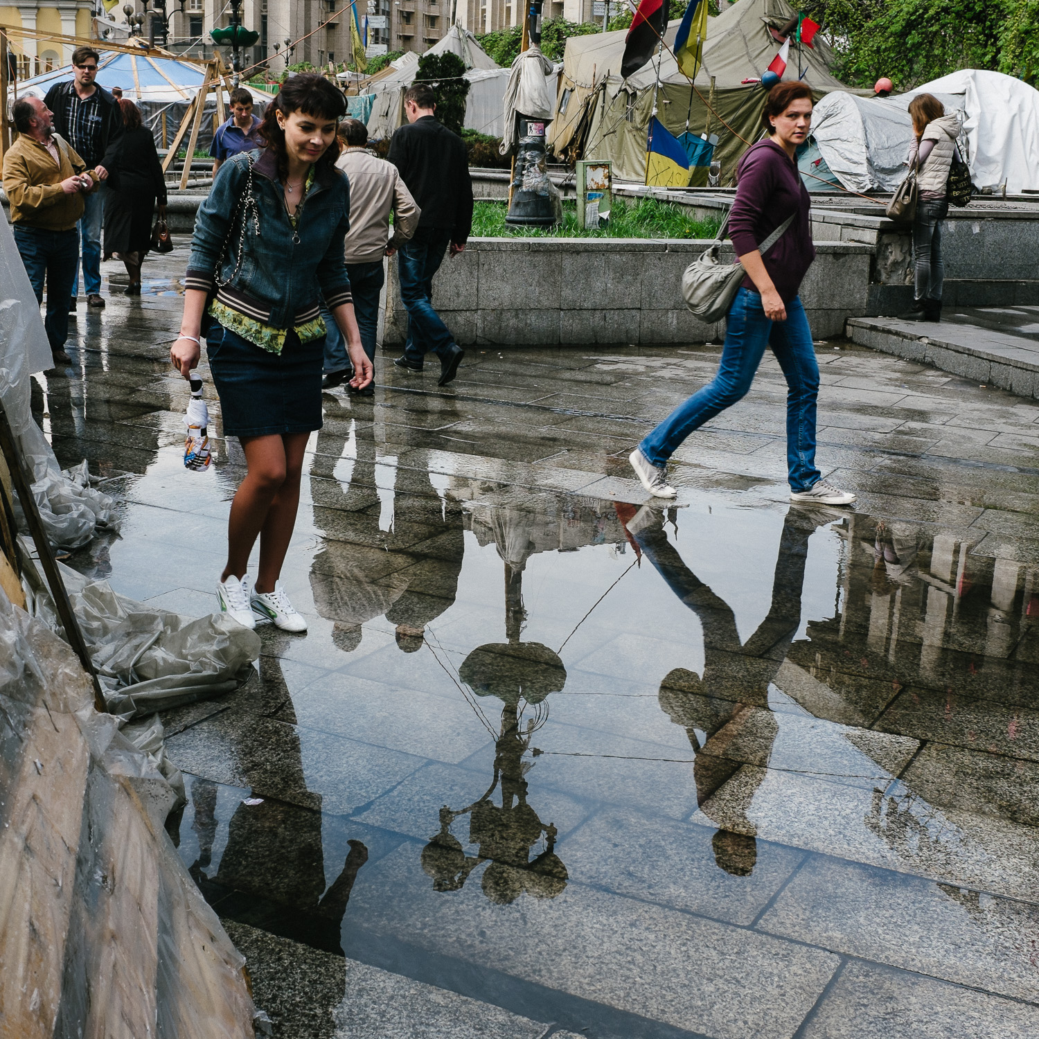 People step around puddles of water after a rain shower on Kiev's Independence Square, April 2014.