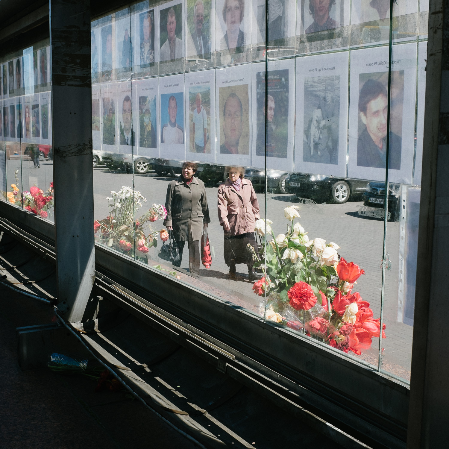Women walk past a display of pictures of those killed in Ukraine's Euromaidan protests, April 2014.