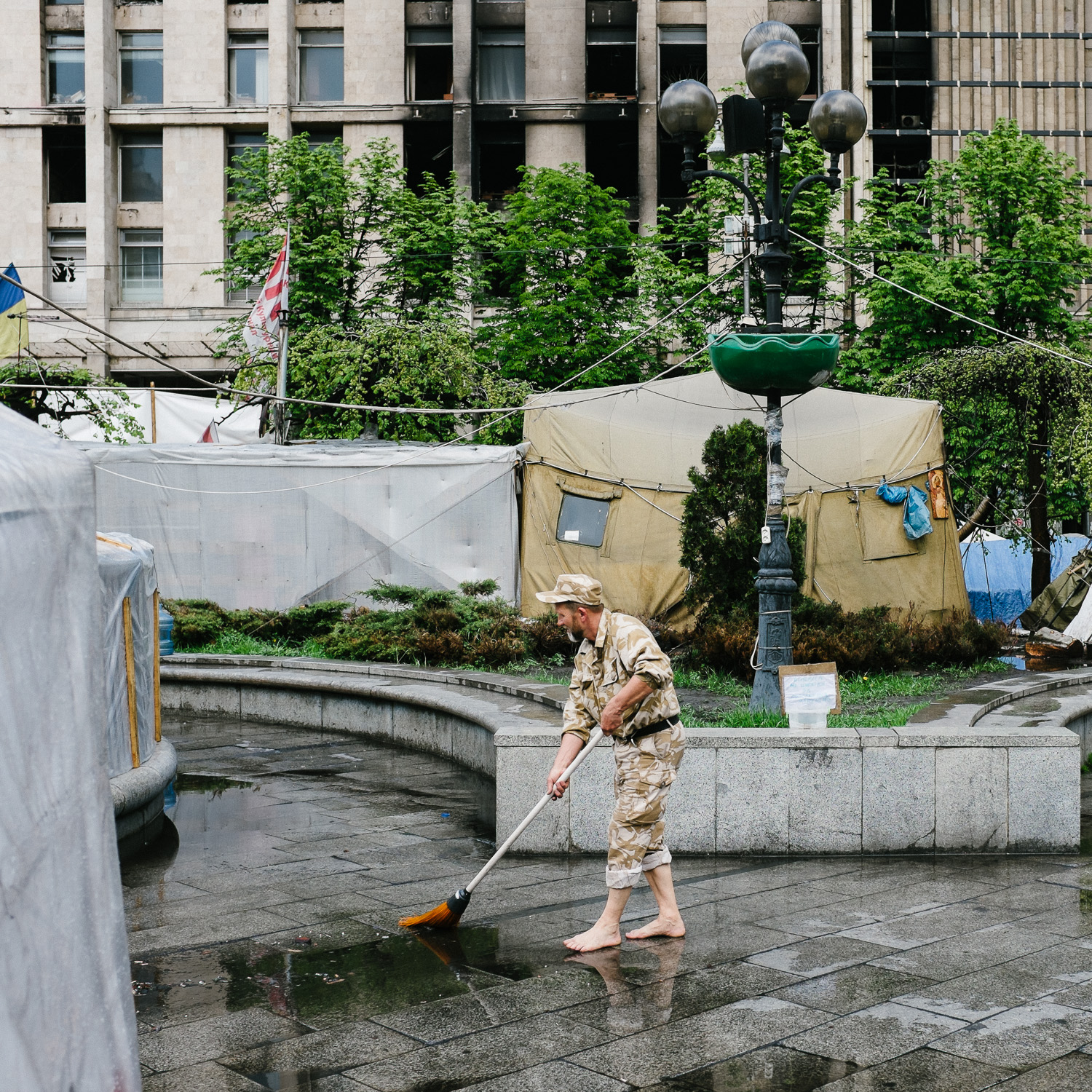A man sweeps away water after rain in Independence Square, Kiev, April 2014.