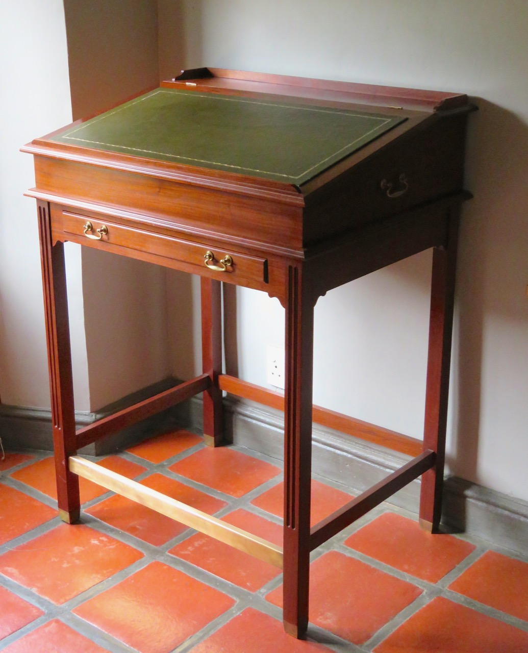 An early piece, a stand-up desk. Honduran mahogany, brass footrest, leather writing surface.