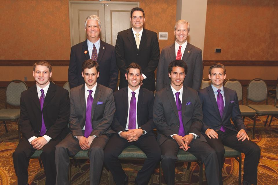 The 2014 Executive Board of the Epsilon Omicron Chapter of Phi Gamma Delta posing after the Chartering Dinner sitting in front of Kappa Omicron Graduate Brothers Alan Thayer and Jake Cramer (EO's Purple Legionnaire), as well as Archon President and Phi Kappa Graduate Brother, Scott Mikulecky.