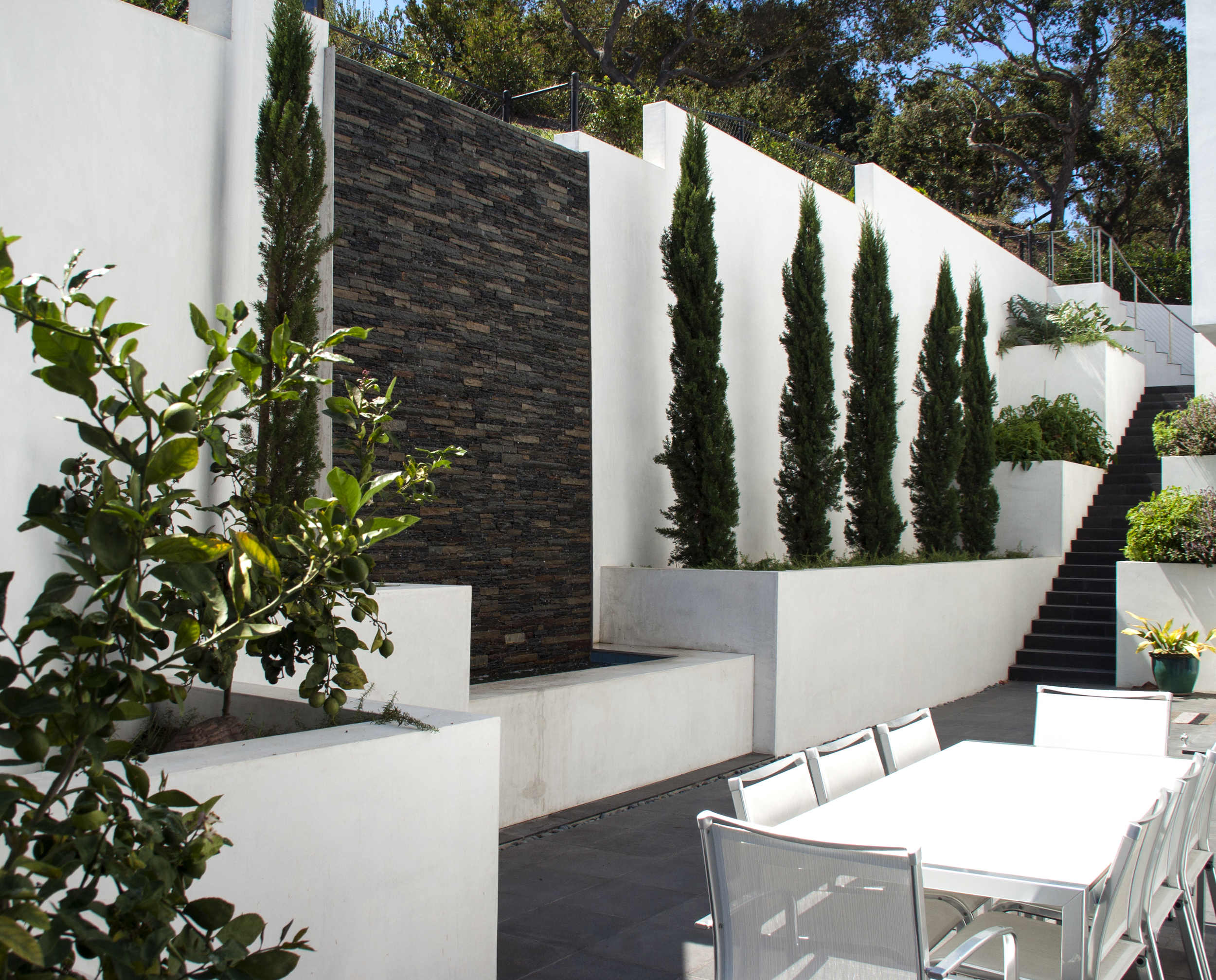A captivating wall water feature with a striking white wall and lush green landscape make for a enjoyable backdrop for any type of gathering.