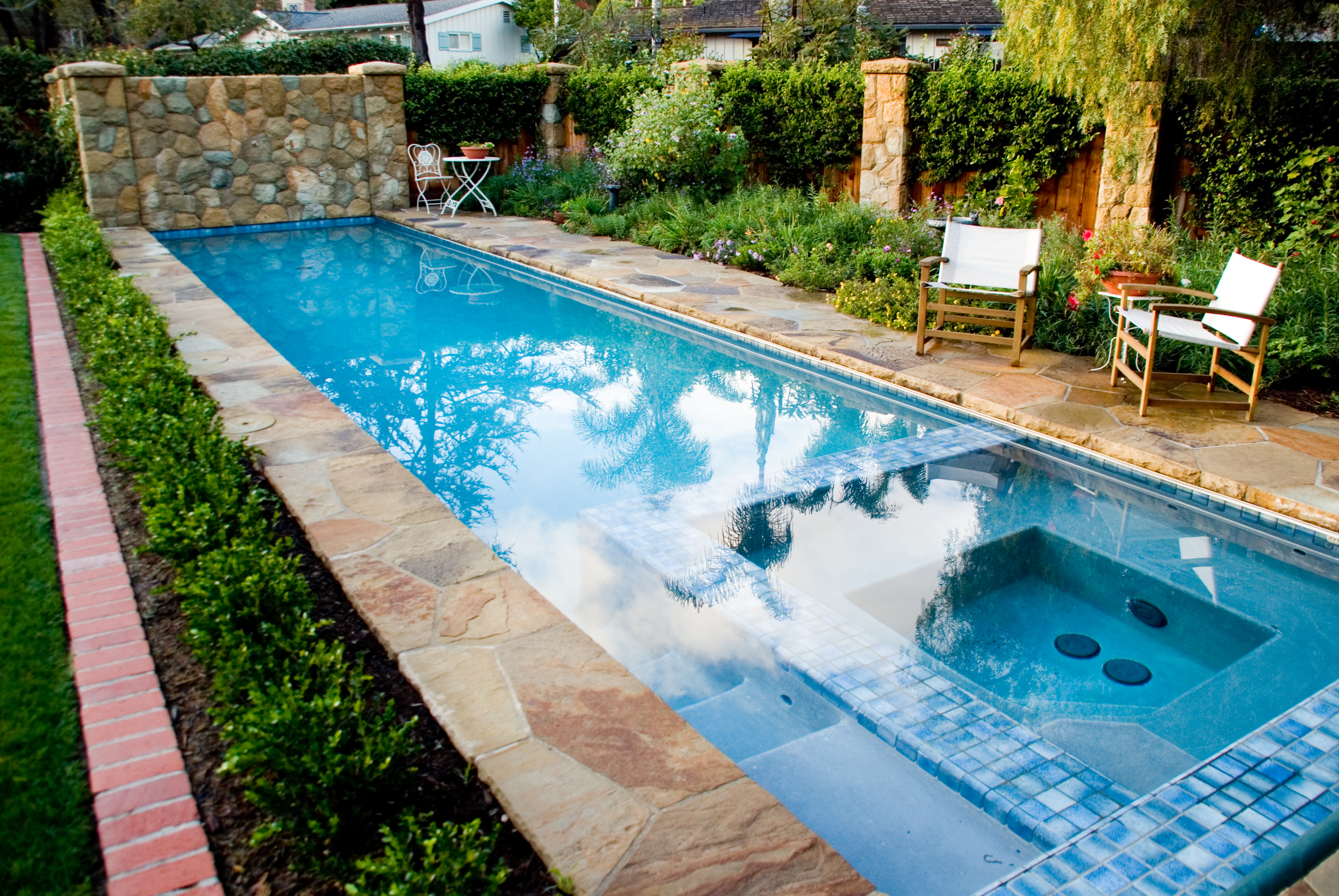 Long swimming pool with inset spa, long gradual steps lead into pool snugly fit between spa and pool side. Decorative variegated blue tile surround spa, blending into the shimmering pool waters.