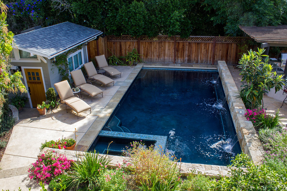 Spacious medium sized pool with built in spa, stairs double as easy entry and pool bench conveniently along spa. Stone wall along back side of pool provides safety next to BBQ entertainment area and provides an opportunity for inventively pleasing triple water falls.