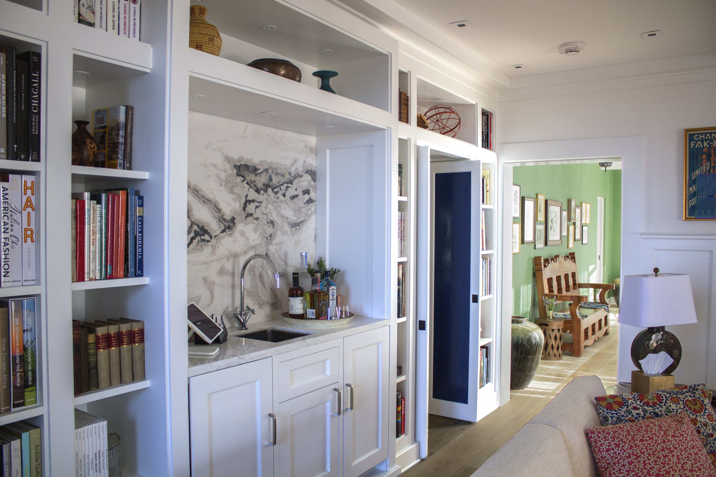 A simple yet refined wet-bar with refrigerator and wine cooler hidden away by wood paneling. Custom built-in shelving with top shelf lighting