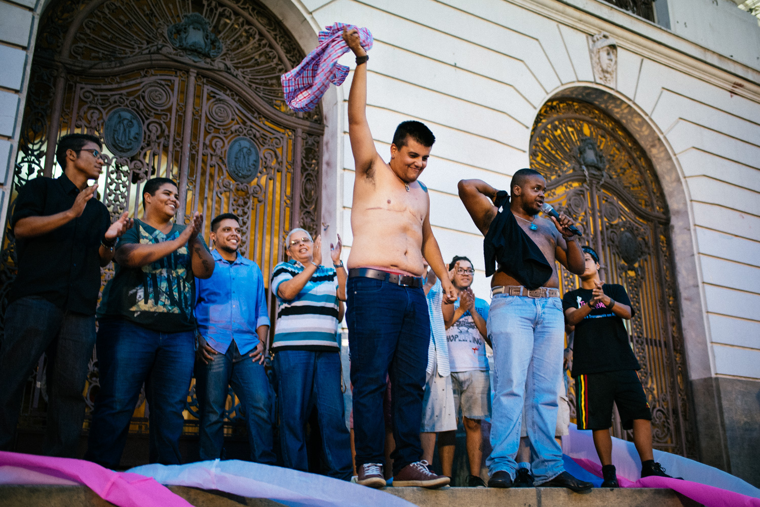 """Transgender men proudly show off their scars from breast removal surgery in front of Rio de Janeiro city hall on transgender awareness day, January 29th, 2015. In a passionate speech they proclaimed their equality among men and to a thunderous applause proclaimed they were """"men with p**sies""""."""