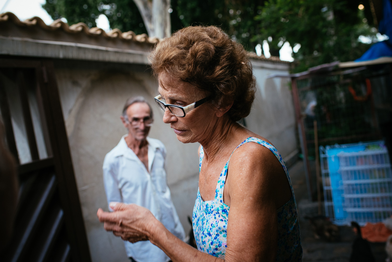 Edina Ferriera Prado, 70, nearly in tears as she gives a puppy away for adoption. Prado said she always fears new owners will mistreat them. Rio de Janeiro, Brazil, 03-15-2015