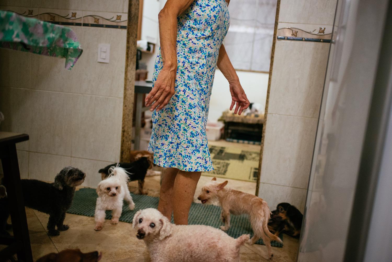 Edina Ferreria Prado, 70, moving through her kitchen, being careful not to step on her many dogs. Rio de Janeiro, Brazil. 03-15-2015