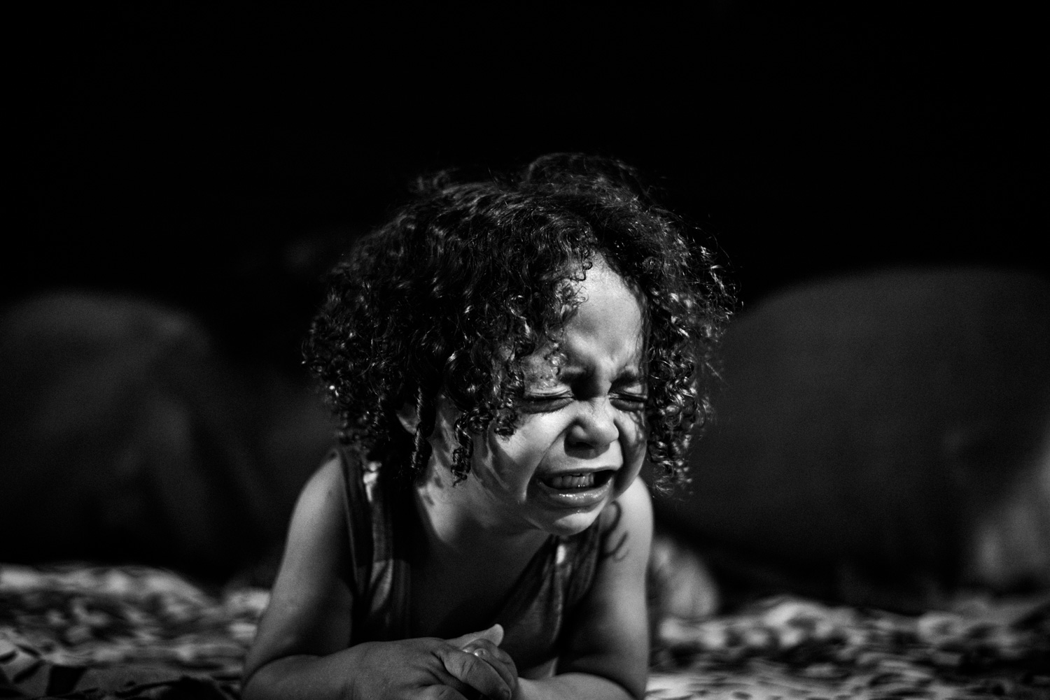 """Kaue, 2, cries for his mother. His dad, Claudio """"CG"""", 24, used to work selling drinks at favela funk parties. He claims to have been earning well over $3,000 USD a month and was living a comfortable middle class life until police shut down the parties."""