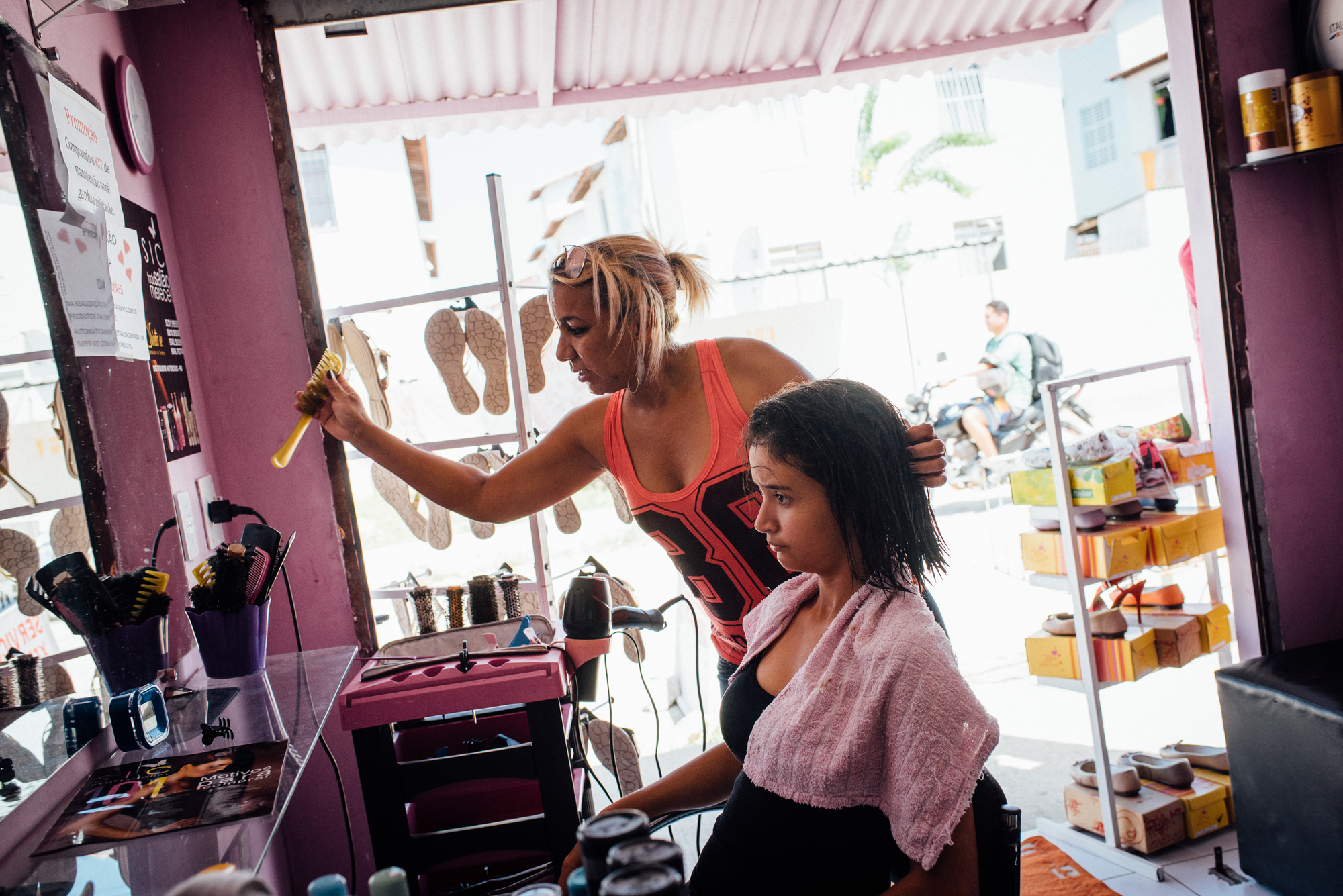 "Eliane Estrela, 43, (center) finishes a client's hair. Estrela opened a beauty salon in front of her house at the Irma Dulce projects in Joao Pessoa. ""Being close, things get better"", she says being both frustrated at how far everything is yet happy to own her own house."