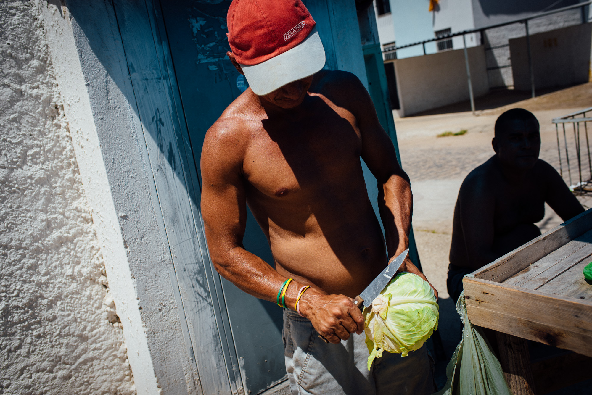 Jose Carlos, 38, cuts a head of lettuce to sell in front on his house. Some residents of the Irma Dulce housing project in Joao Pessoa, far removed from the city center, have opened up shops in front of their houses.