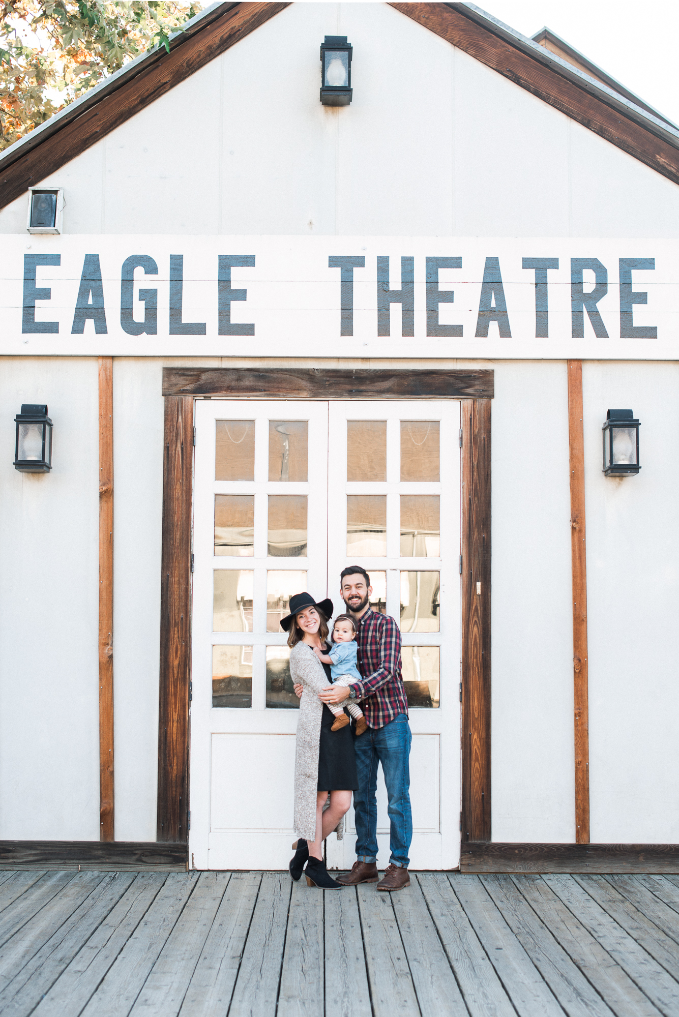 family smiling in front of Eagle Theater