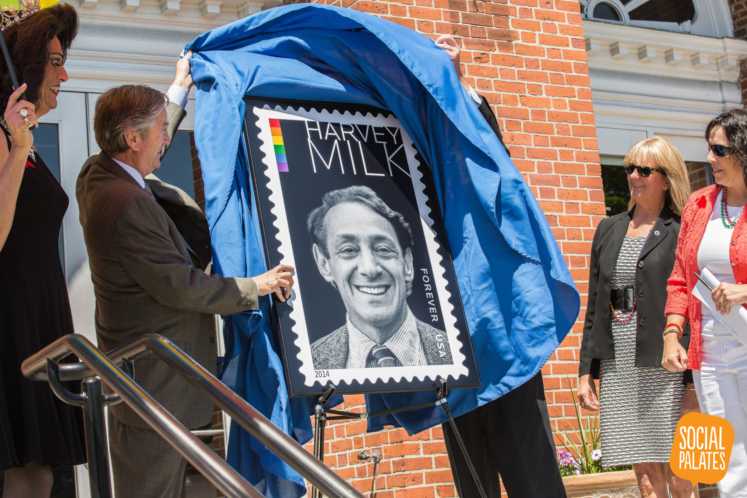 Congressman John Tierney and Salem Postmaster Mark Howell unveil the Harvey Milk Forever Stamp alongside Mayor Kim Driscoll, State Senator Joan Lovely, the Queen of Salem Gigi Gill, and other LGBT activists and supporters on June 1, 2014.