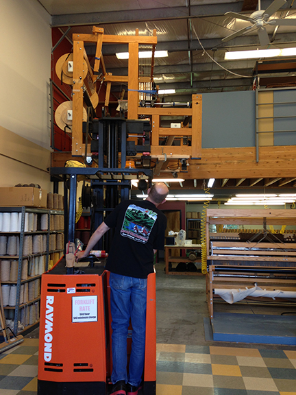 Using a forklift to get the small loom downstairs.