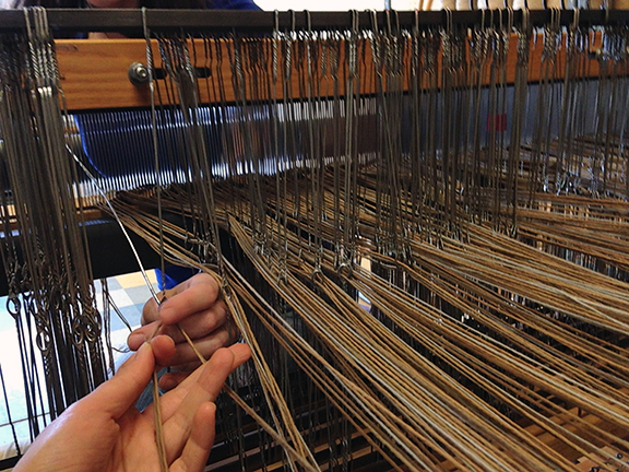 Threading the heddles.