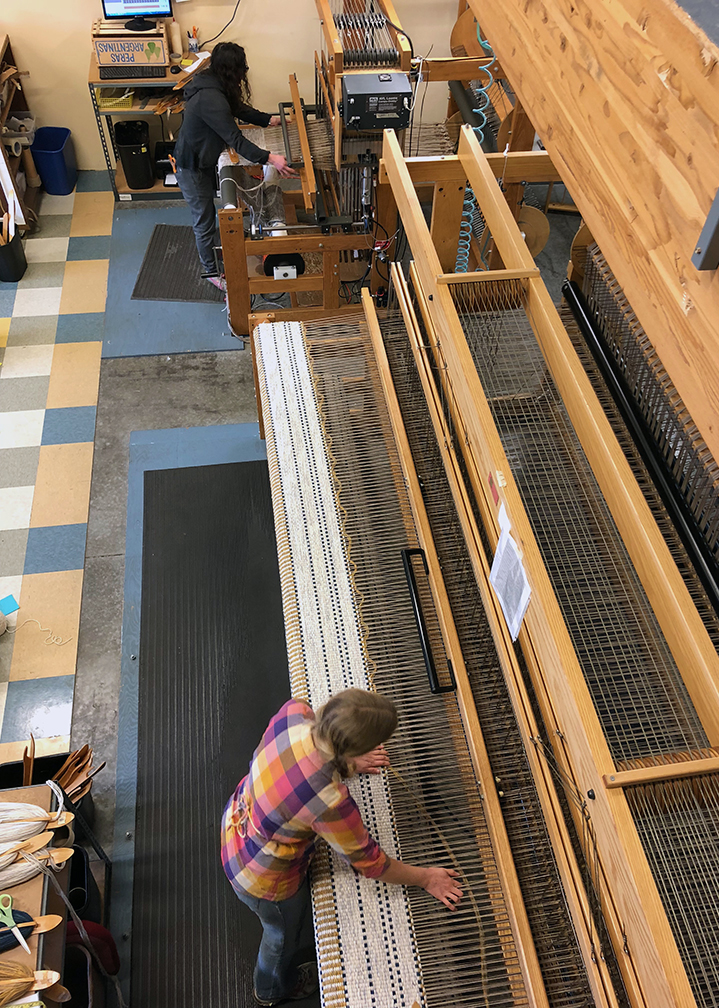 Aurora weaving on Dotted Line rug. Michelle weaving a runner.