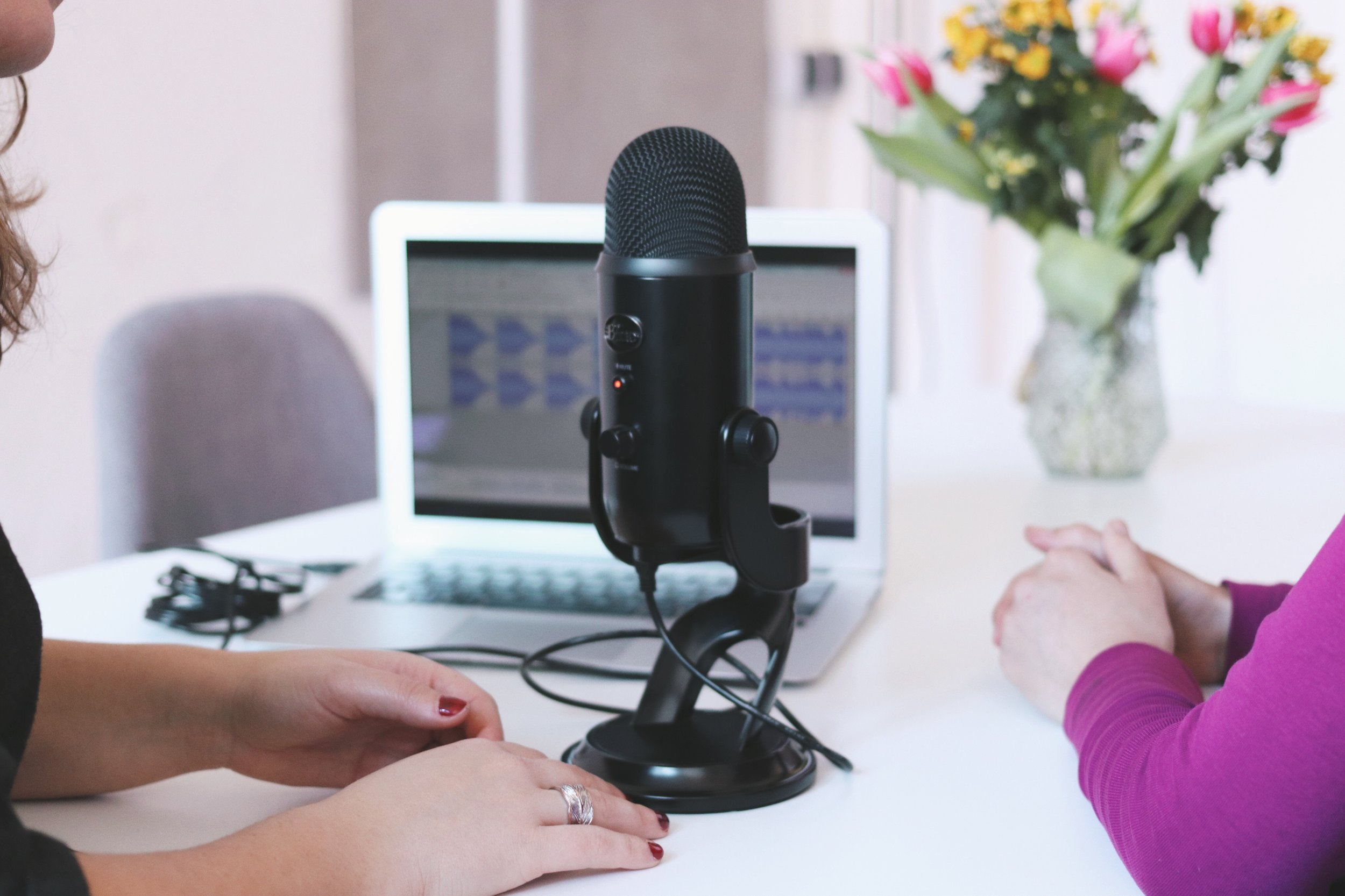 A USB microphone (Blue Yeti) and two women recording a podcast