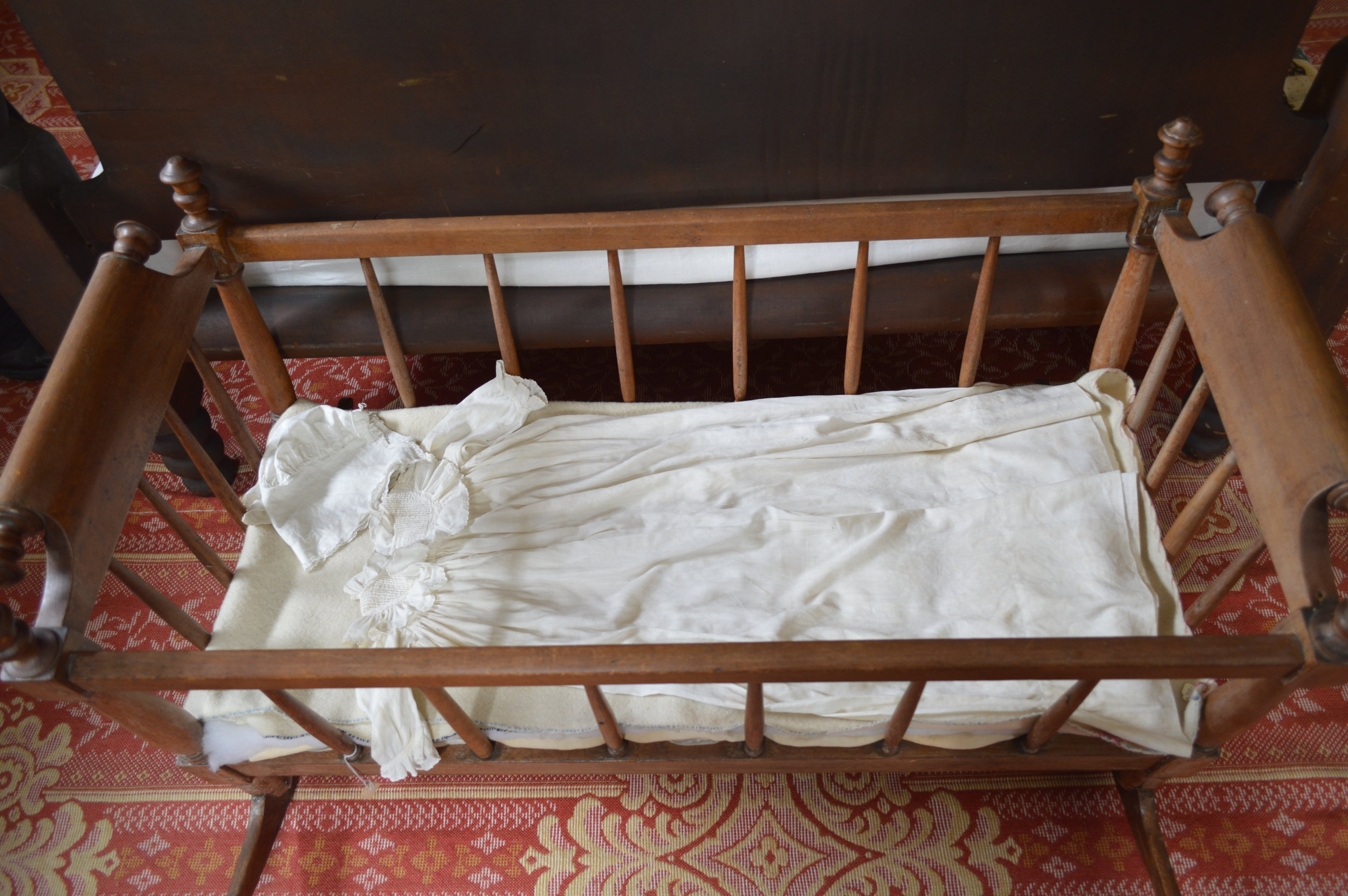 Next to the parents' bed was a rocking cradle with a laceembroidered cap and gown for the baby.