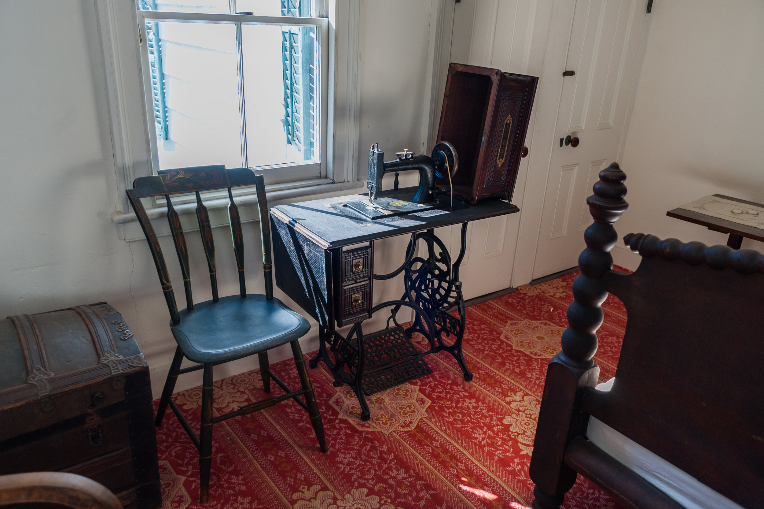 A later model sewing machine was placed in the master bedroom. The pattern of the carpet is Linderwald. It was copiedfrom the 1856 James Van Buren House in Kinderhook, New York.